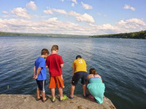 Kids fishing on the dock at Lake Cayuga